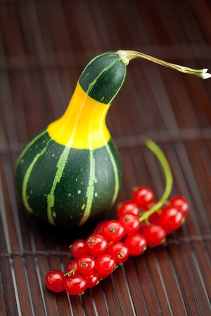 yellow green china pumpkin and red currants on a bamboo mat photo