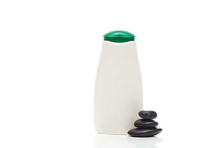 cosmetic containers and spa black stones isolated on white photo