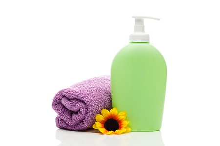 cosmetic containers, towel and flower isolated on white photo