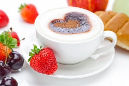 cappuccino in a cup in the shape of hearts,cherry,croissant  and strawberries isolated on white