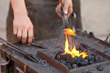 red hot iron: embers, fire, smoke, tools and the hands of a blacksmith Stock Photo