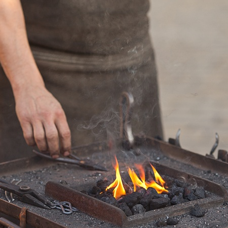 embers, fire, smoke, tools and the hands of a blacksmith photo