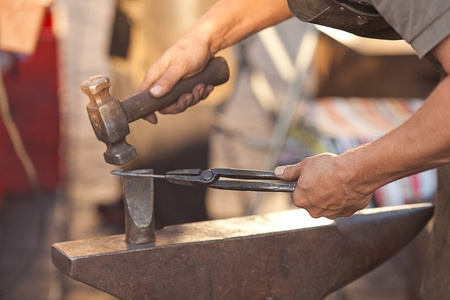 hammer, anvil and the hands of a blacksmith