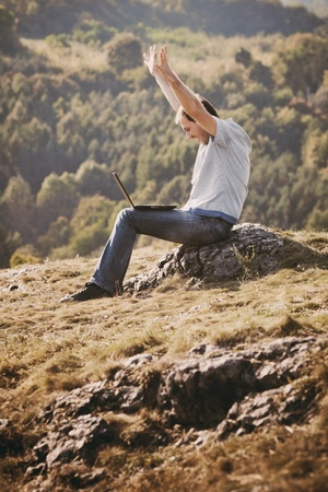 young man using laptop sitting on the grass on the hillside photo