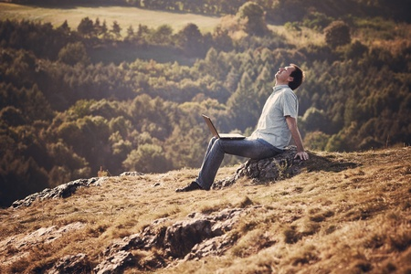behind scenes: young man using laptop sitting on the grass on the hillside