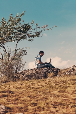 behind scenes: young man using laptop sitting on a hill against the blue sky
