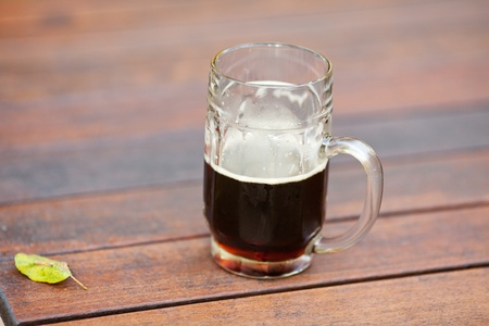 mug with dark beer standing on the table photo
