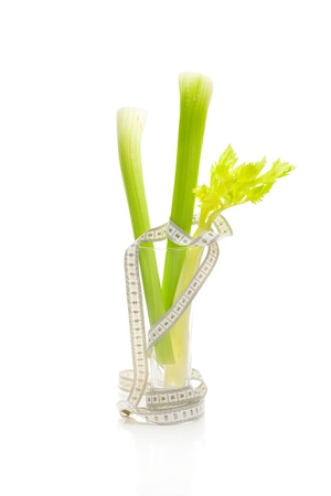 celery in a tall glass and measure tape isolated on white photo
