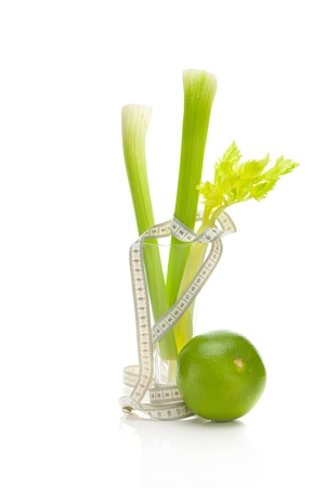 celery in a tall glass, green grapefruit and measure tape isolated on white photo