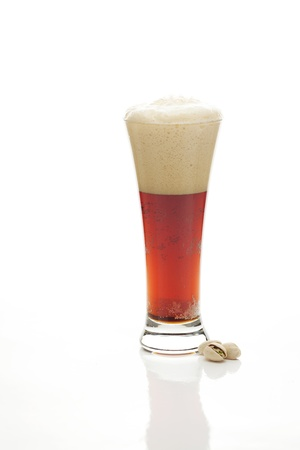 dark  beer with the foam in a tall glass and pistachios isolated on white photo