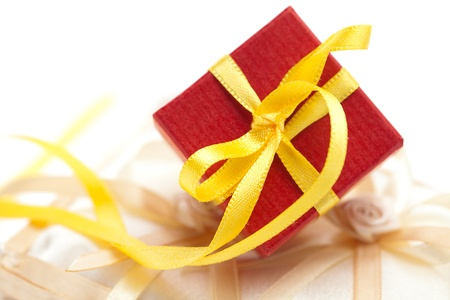 red gift box with a yellow ribbon on a cushion for the rings photo