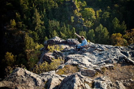 young man using laptop sitting on a rock slope photo