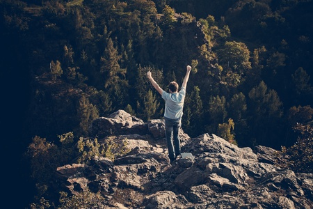 young man standing on a rock slope photo