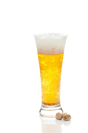 light beer with the foam in a tall glass and pistachios isolated on white photo