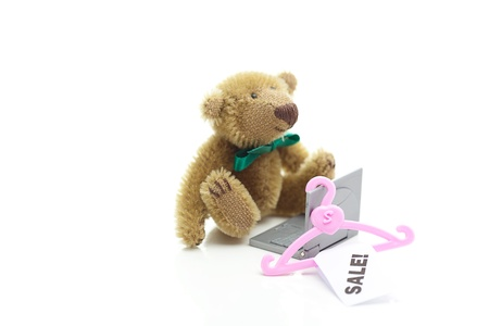 teddy bear,hanger with a price tag sale and miniature laptop  isolated on white photo