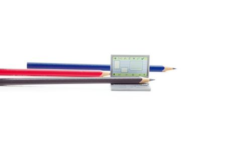colored pencils and miniature laptop isolated on white photo