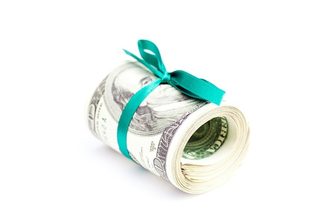 Dollars rolled into a tube tied with ribbon isolated on white photo