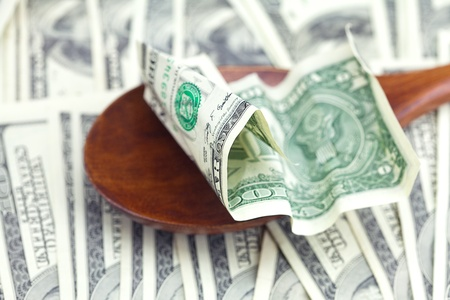 Dollars in the wooden spoon on dollars background Stock Photo - 11932791