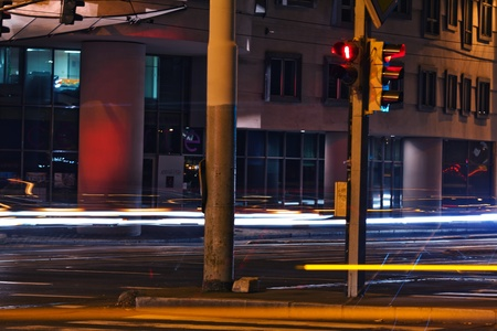 strip from passing cars and traffic lights at night street photo