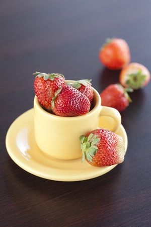 strawberries and a cup with saucer on a wooden table photo