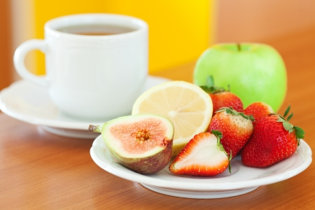 cup of tea, apple, lemon, fig and strawberries on a plate photo