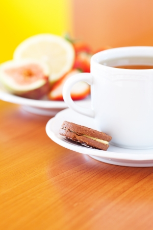 cup of tea,cookie, lemon, fig and strawberries on a plate photo