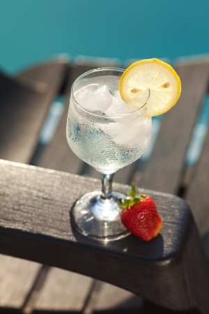 Swimming pool, lounge, a wine glass with ice, lemon and strawberry photo