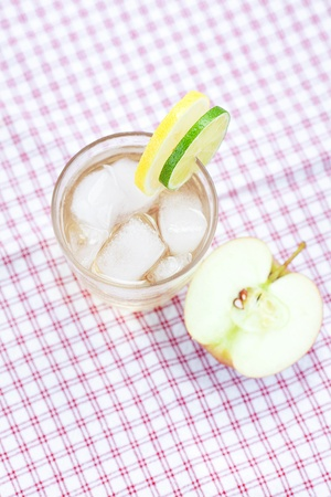 water with lemon and lime,apple in a glass with ice photo
