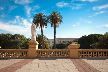 balcony with a statue on a background of palm trees and blue sky photo