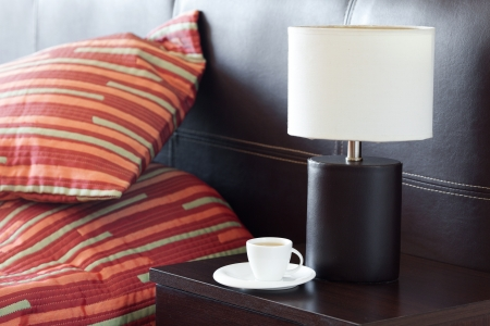 bed with a pillow, a cup of tea on the bedside table and lamp Stock Photo - 13710537
