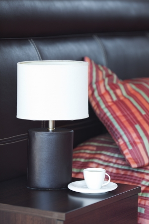 bed with a pillow, a cup of tea on the bedside table and lamp Stock Photo - 13710526
