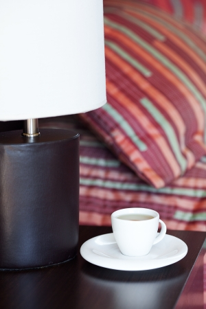 bed with a pillow, a cup of tea on the bedside table and lamp Stock Photo - 13710542