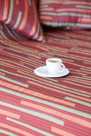 bed with two pillows, a cup of tea on the blanket Stock Photo
