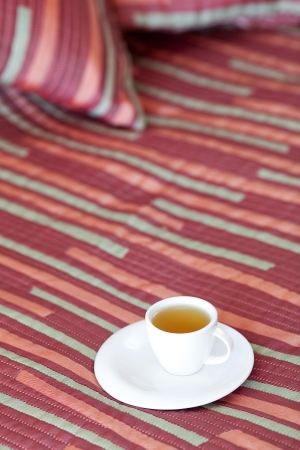 bed with two pillows, a cup of tea on the blanket Stock Photo - 13710550