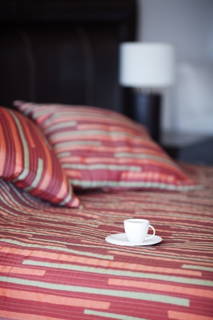 bed with a pillow, a cup of tea on the bedside table and lamp Stock Photo - 13710541