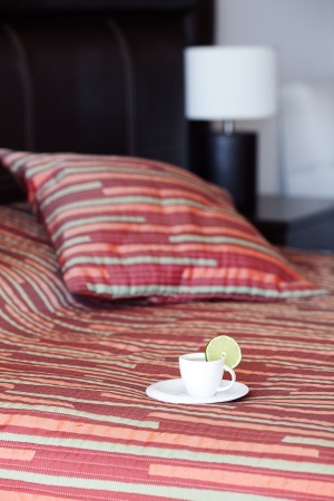 bed with a pillow, a cup of tea on the bedside table and lamp Stock Photo - 13710553