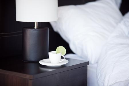 cama: cama con una almohada, una taza de t� sobre la mesita de noche y l�mpara