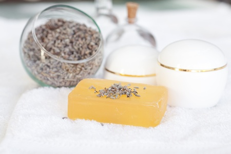 cosmetic containers, bottles, soap and lavender on a white towel photo