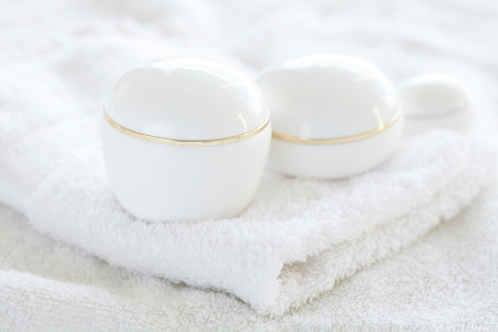 cosmetic containers lying on white towel photo