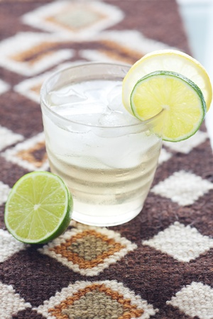 water with lemon and lime in a glass with ice on ethnic mat photo