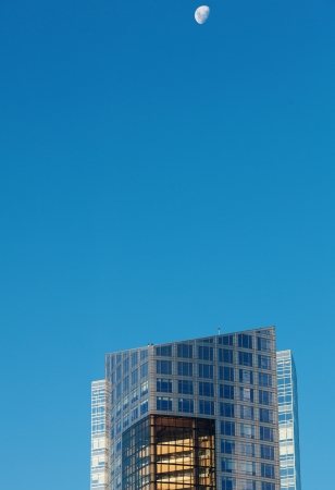 Beautiful modern office buildings and the moon against the blue sky photo