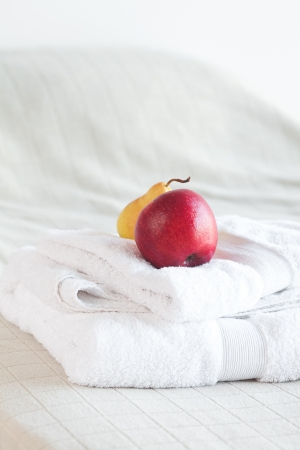 apple and pear on towels on the bed  photo