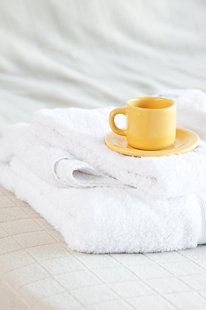 cup lying on towels on the bed  photo