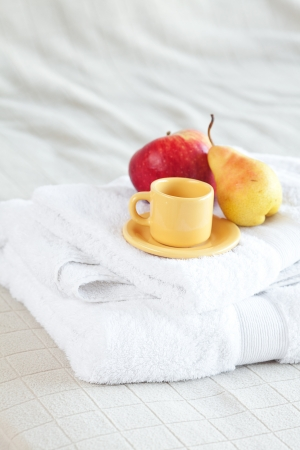 cup,apple and pear on towels on the bed  photo