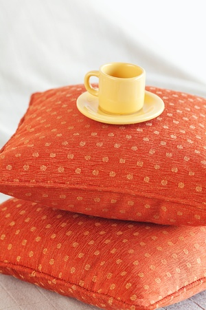 cup lying on pillows on the bed photo