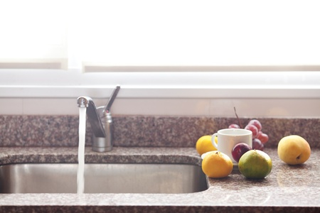 cup, fruits and faucet on the kitchen photo