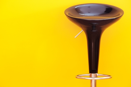 bar chair against a yellow wall in the apartment photo