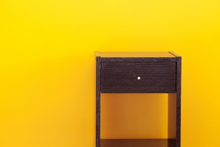 nightstands: bedside table against a yellow wall in the apartment