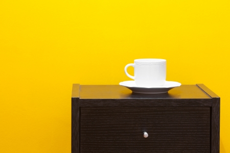 nightstands: bedside table and cup against a yellow wall in the apartment Stock Photo