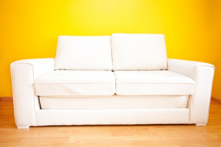 white sofa against a yellow wall in the apartment photo